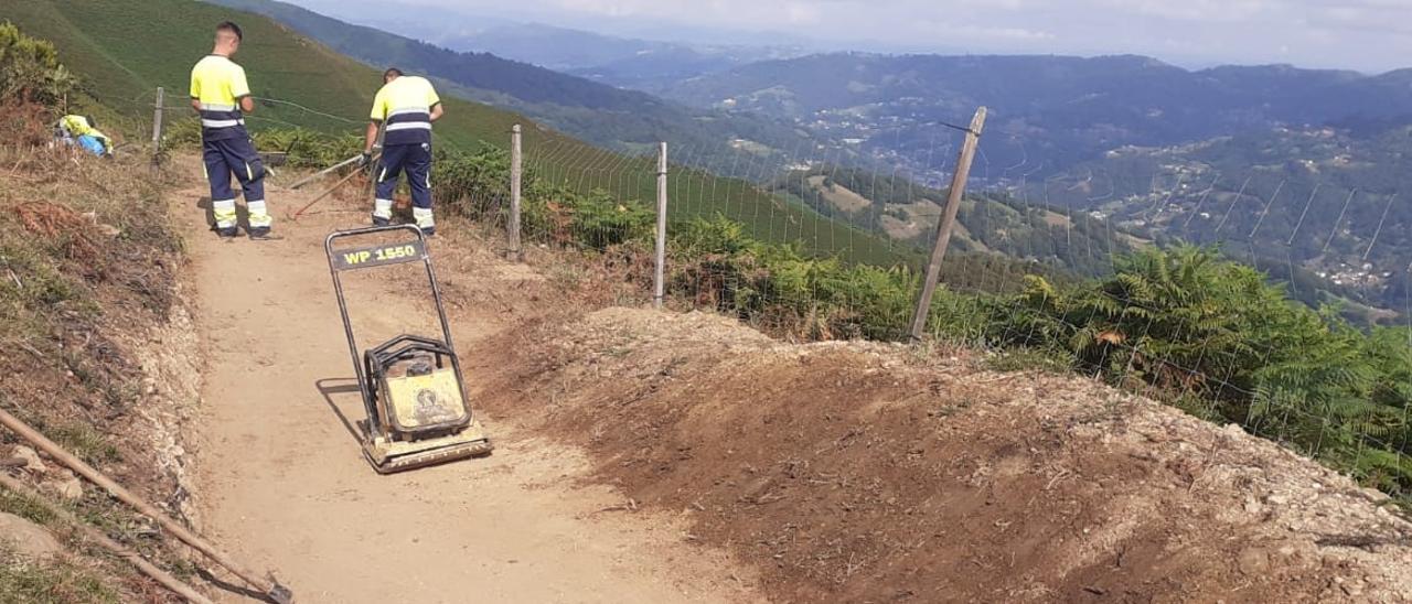 """Dos trabajadores realizan algunas de las últimas tareas en el descenso """"flow trail"""" que se inaugurará el próximo día 19 en Laviana."""