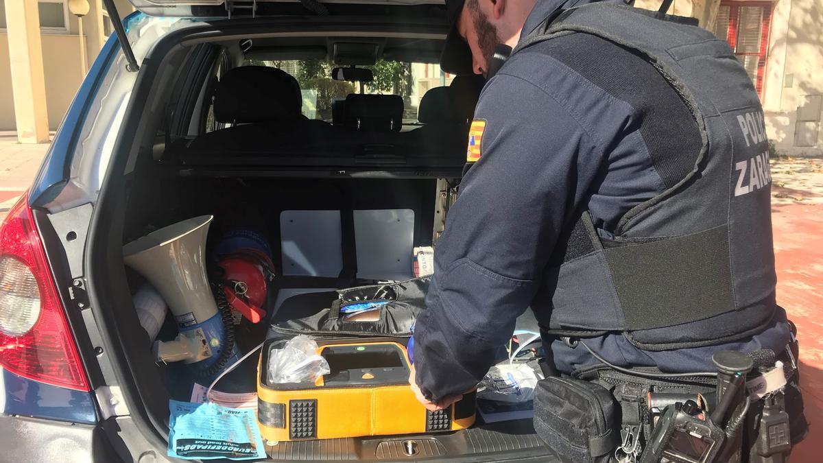 Archivo - Un agente de Policía Local comprueba un defibirilador