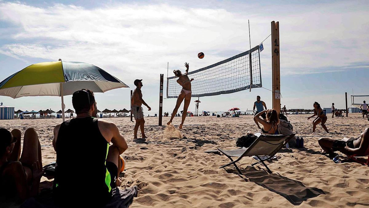 Un grupo de personas en la playa de la Malvarrosa de València juega al voleibol y toman el sol.    ANA ESCOBAR /EFE