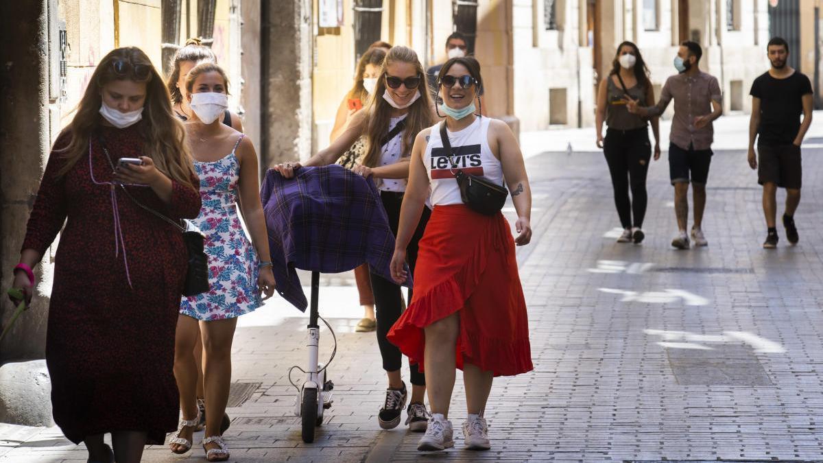 Varios vecinos de València caminan por las calles del centro de la ciudad con mascarilla.