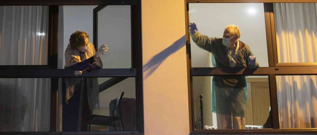 José Manuel Fernández Cándano saluda a su mujer, Nieves Suárez, por la ventana tras recibir el alta en abril. | Miki López