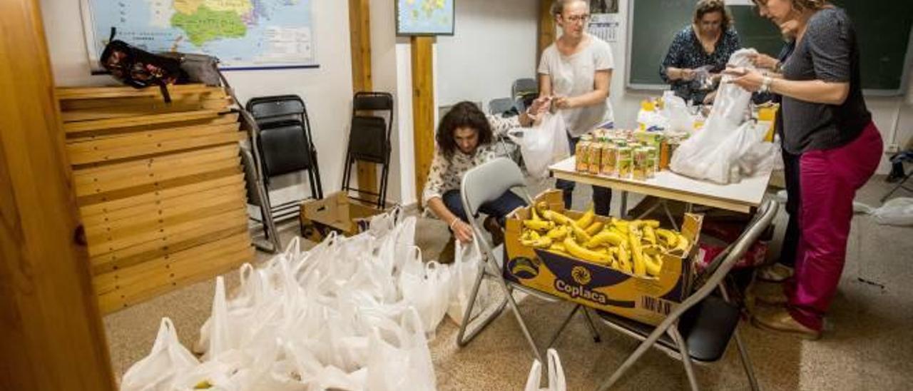 Las bolsas para los indigentes se preparan en un local de Cáritas en Sant Joan.