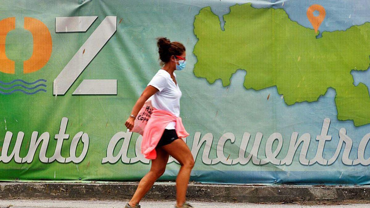 Una mujer con mascarilla camina ante un cartel publicitario de Foz, en la Mariña lucense.