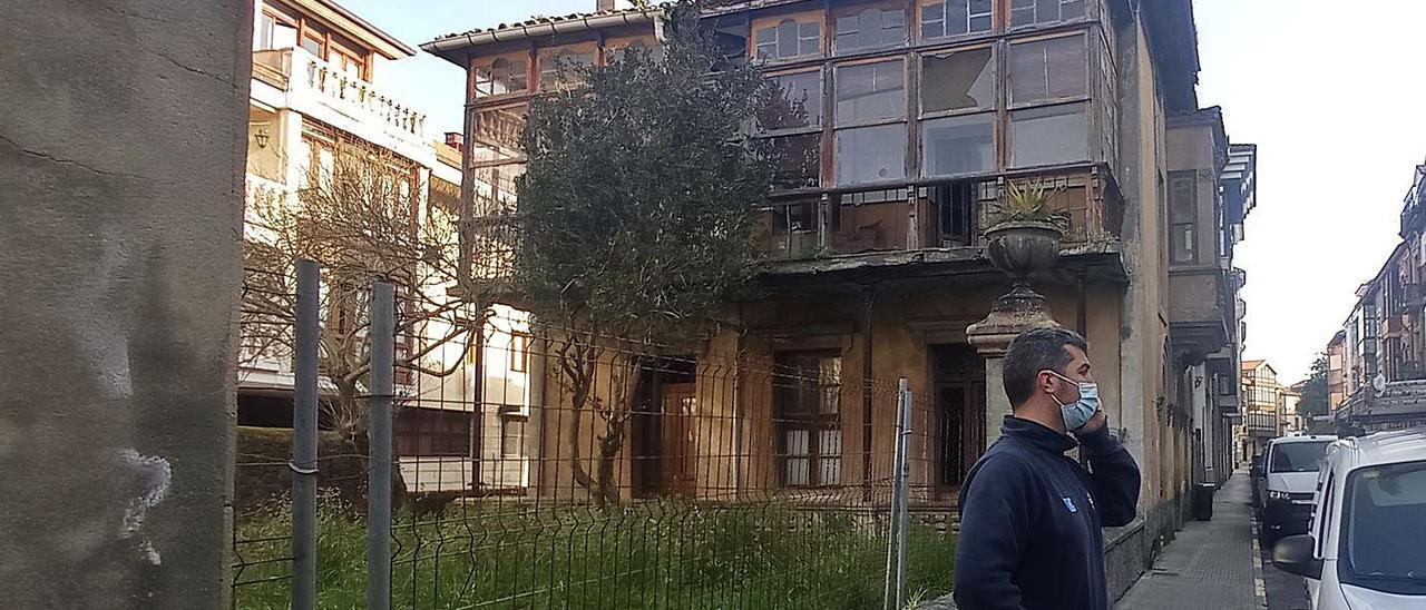 Un vecino, ayer, hablando por teléfono junto a la casa de Gracia Noriega, en Llanes. | Eva San Román