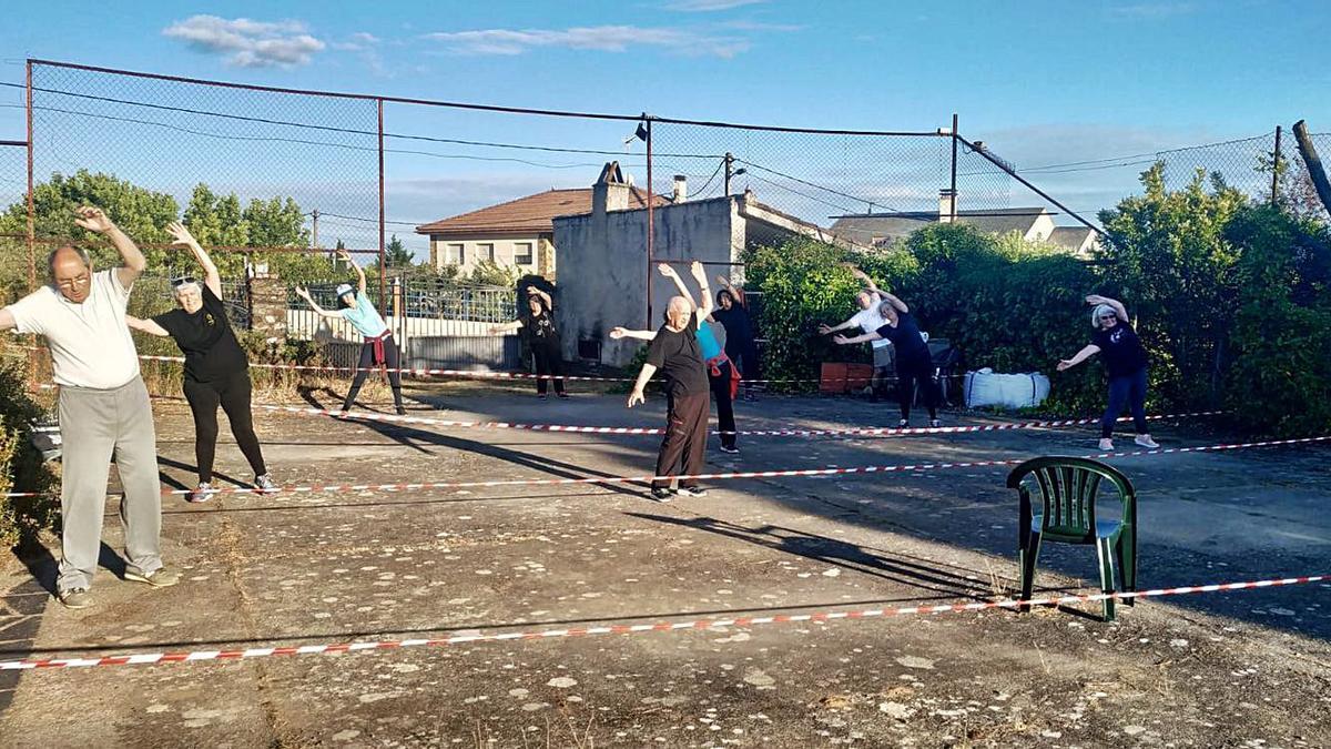 Un grupo de personas realiza ejercicios de gimnasia en una pista de tenis de Alcañices.   Ch. S.