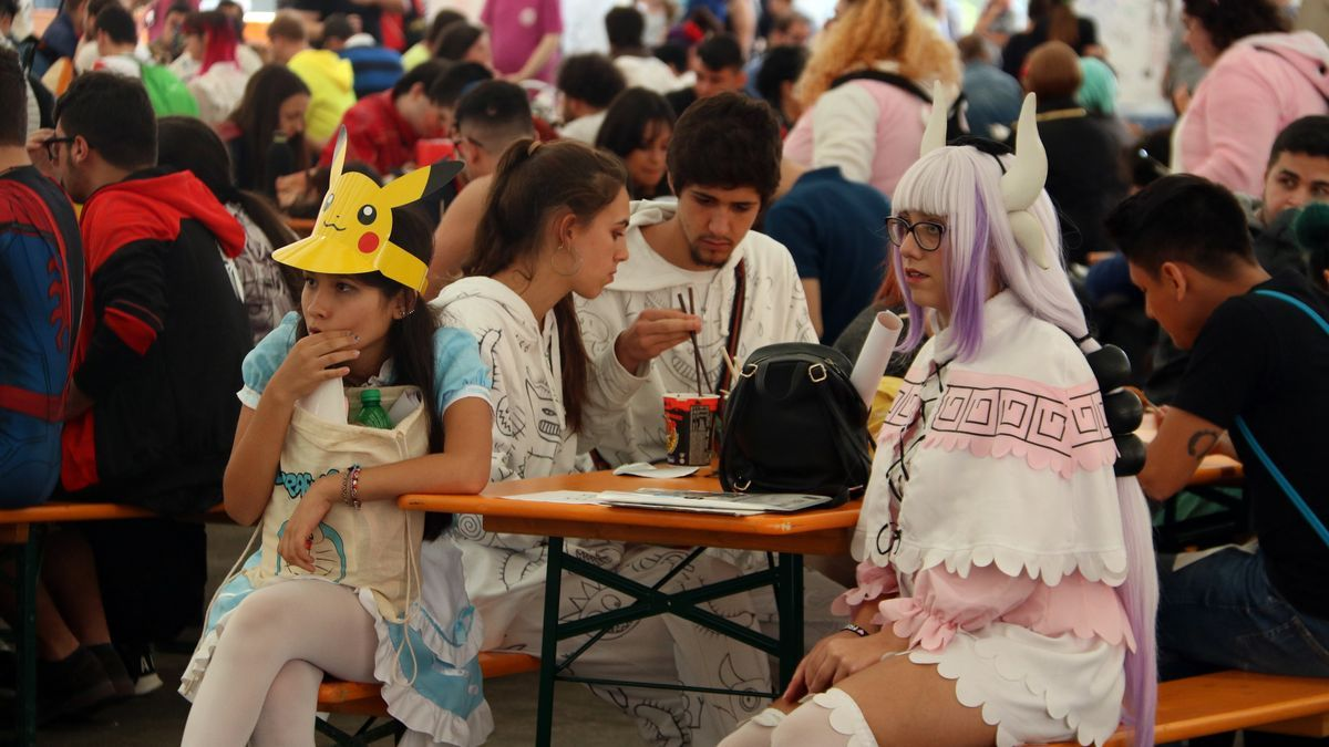 """Dues noies """"cosplaiades"""" entre els assistents al 25è Manga Barcelona, en una zona de descans davant l'escenari."""