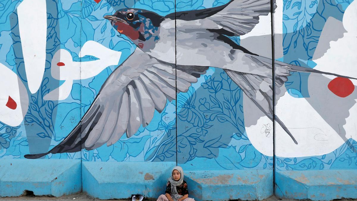 Una niña limpiabotas espera a los clientes bajo un grafitti en Kabul.