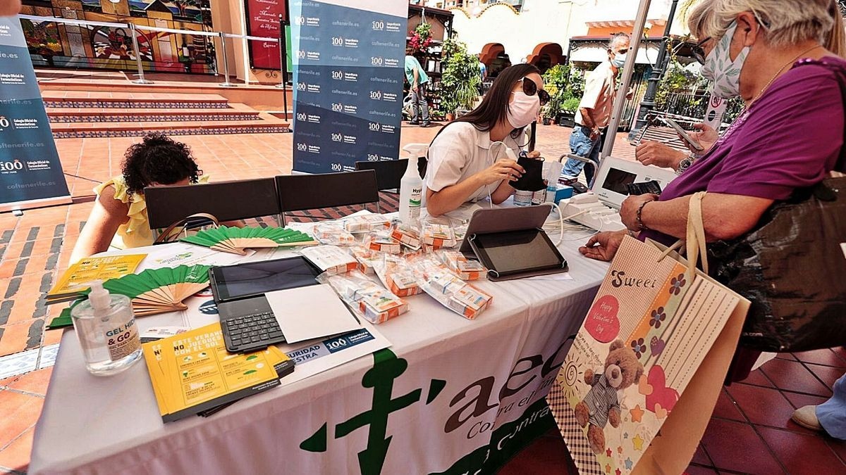 Personal farmacéutico en el momento de hacer una prueba a una vecina en el Mercado Nuestra Señora de África, en Santa Cruz de Tenerife.