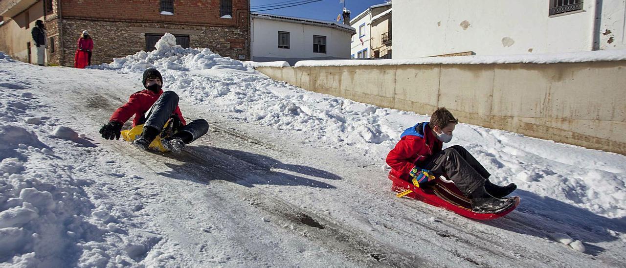 Dos niños se deslizan por  una cuesta de nieve, ayer,  en Sinarcas. f.bustamante.