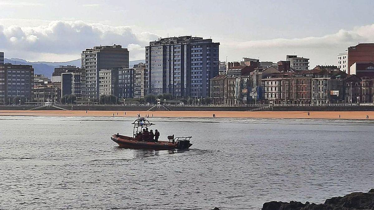 Voluntarios de rescate de Cruz Roja, durante las labores de búsqueda ayer por la mañana en la playa de San Lorenzo, en Gijón.