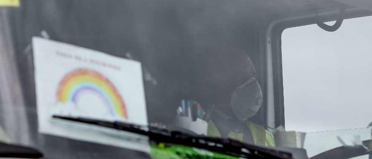 Un transportista conduce por el polígono de La Peñona de Gijón con mascarilla.