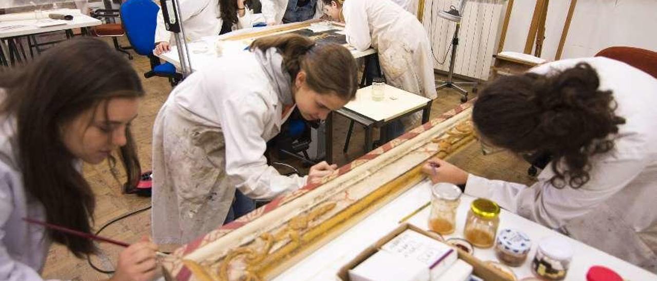 Alumnas, ayer, durante la jornada de puertas abiertas en el taller de restauración de pintura, con la profesora Gemma Puente Peinador.
