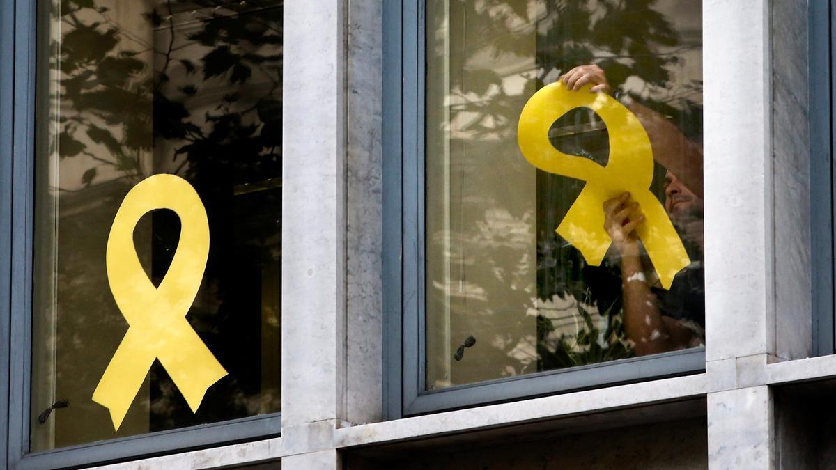 Un hombre coloca lazos amarillos en la ventana de un edificio de Cataluña