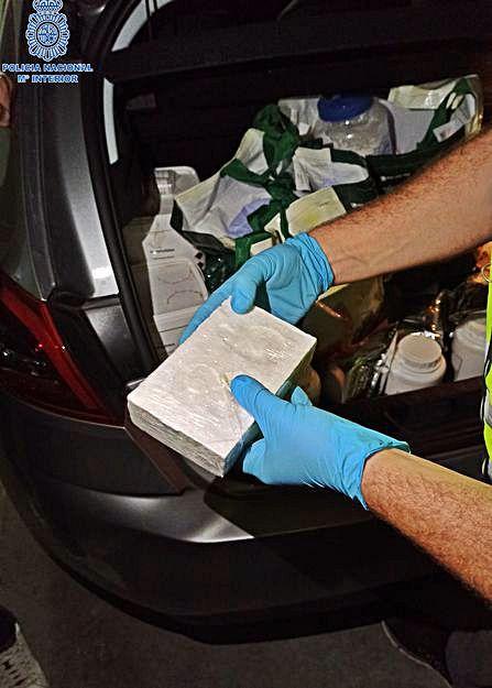 Un policía examina un ladrillo de cocaína.