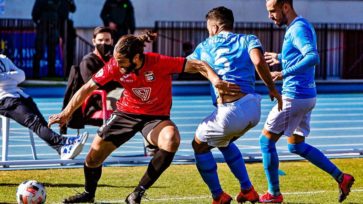 El delantero Mariano Sanz, que redebutaba ayer, controla el balón ante dos jugadores del Ibiza.   DAVID REVENGA
