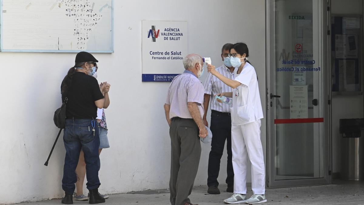 Una sanitaria toma la temperatura a un usuario antes de acceder al centro de salud.
