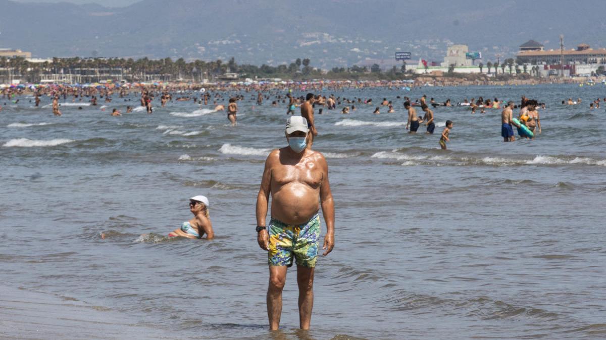 Un hombre, este martes, paseando por la orilla con mascarilla en la playa de Las Arenas.