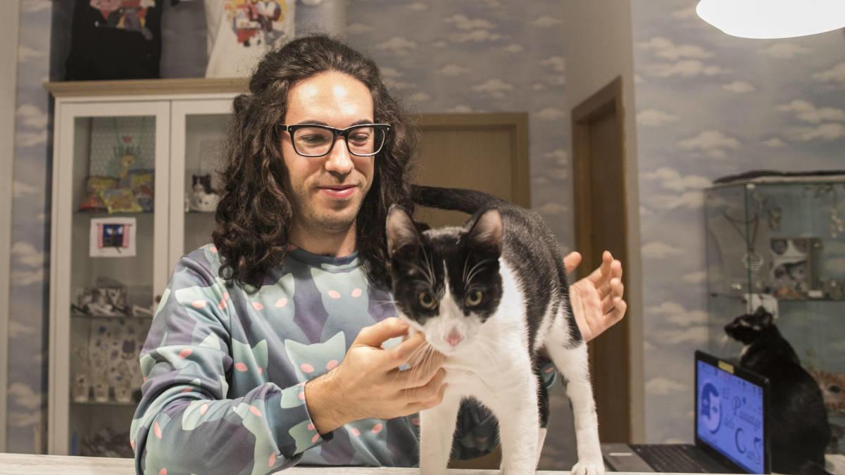El propietario del Catcafé con uno de los felinos.