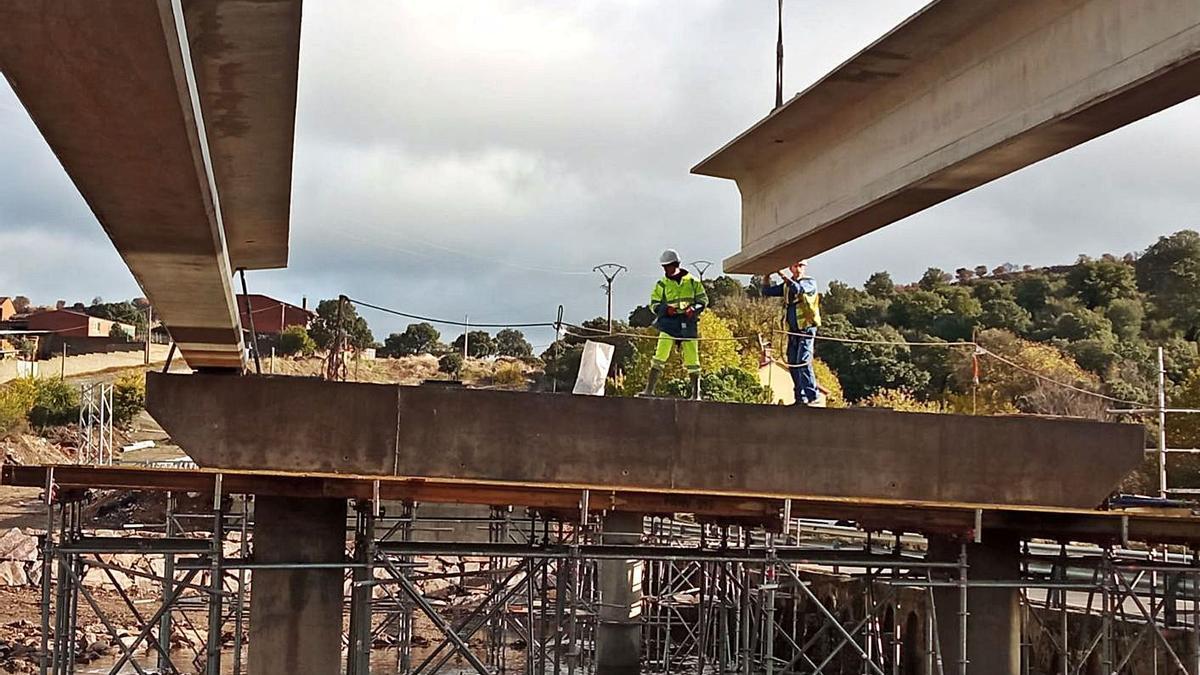 Trabajadores de la construcción colocan una viga.