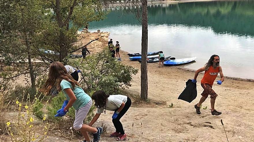 Una quinzena de persones recullen deixalles a la riba del pantà de Sant Ponç