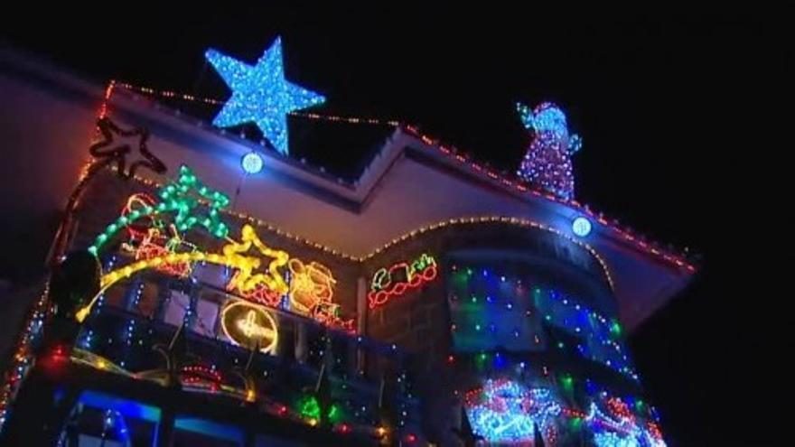 Una casa decorada con cientos de luces y adornos de Navidad