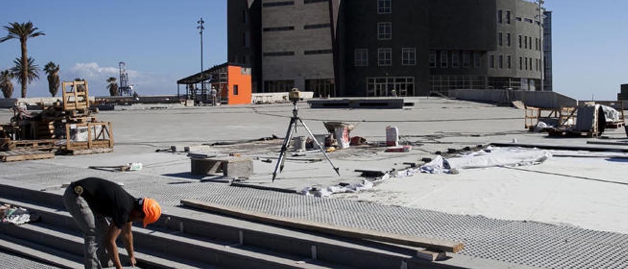 Un operario ultimando la taquilla a la entrada del edificio.