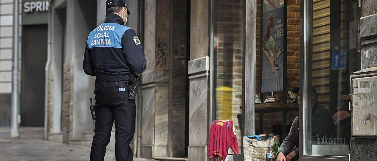 Un policía local habla con una persona sin recursos en una calle de una de las capitales de Canarias.     CARSTEN W. LAURITSEN