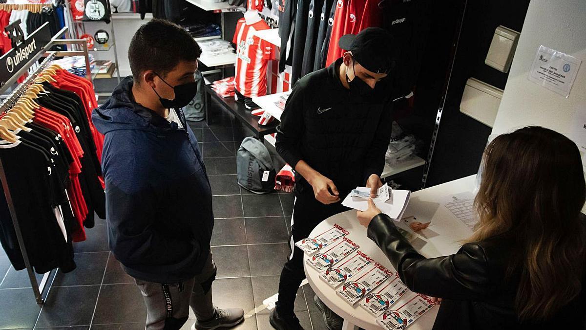Dos aficionados, en al tienda del club rojiblanco, adquiriendo las entradas para el partido del domingo contra el Valladolid Promesas. / Emilio Fraile