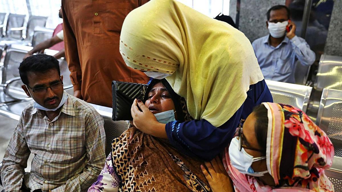 Dos mujeres, familiares de las víctimas, se abrazan en la sala de espera del hospital.   Reuters