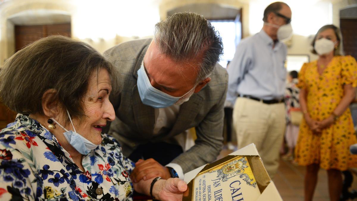 El alcalde entrega el azulejo a Agustina, con familiares al fondo.