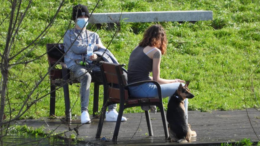 Jóvenes charlando en un parque con mascarilla y distancia de seguridad.