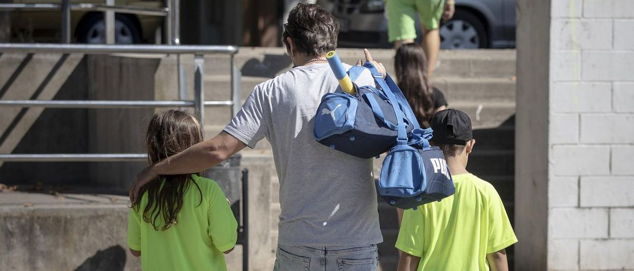 Un padre carga con las bolsas de deporte de sus hijos.