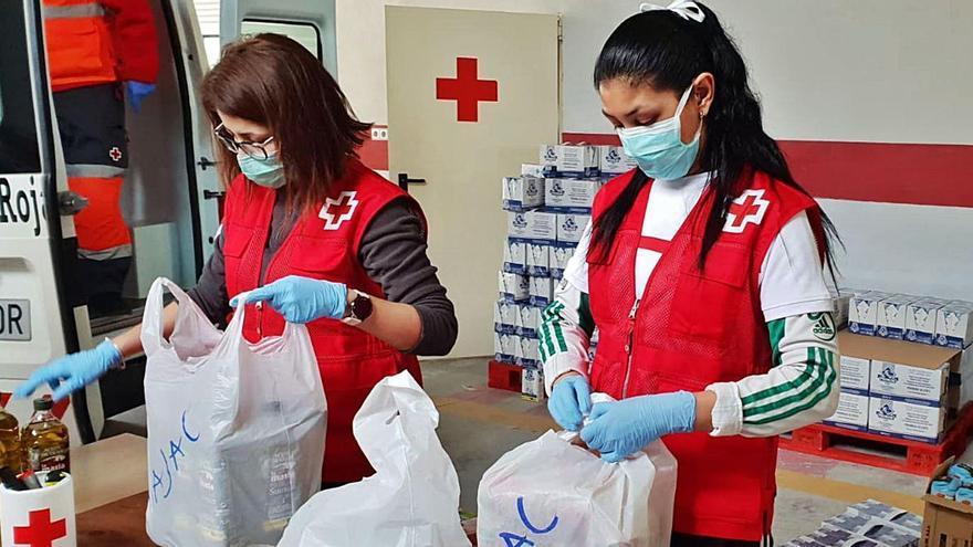Dos voluntarias preparan las cestas de comida para las familias que necesitan ayuda.  | C.R.