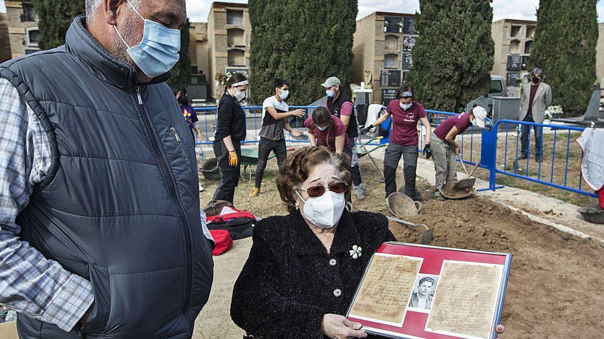 María Ros, junto a las excavaciones en el cementerio, con una foto de su padre y las dos últimas cartas que escribió antes de ser fusilado.