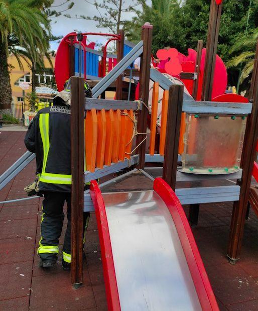 Imagen del rescate de la menor atrapada en un tobogán del parque infantil.