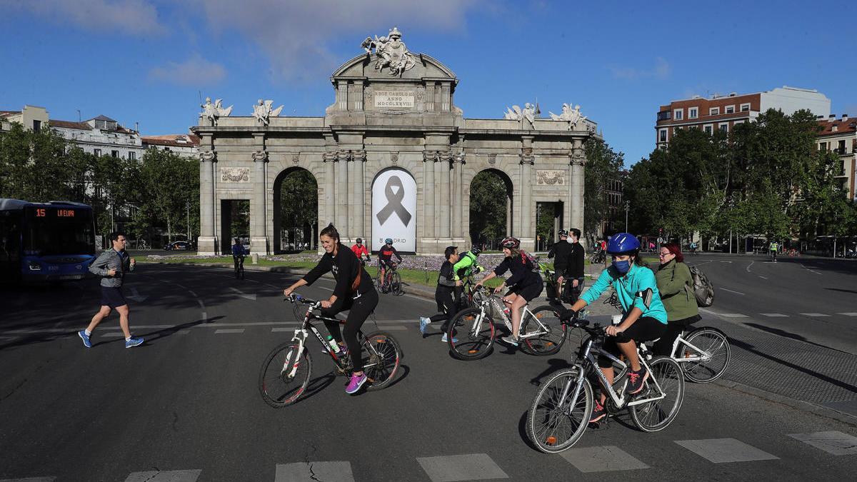 Vista de la Puerta de Alcalá con un crespón junto a la gente haciendo deporte, en Madrid.