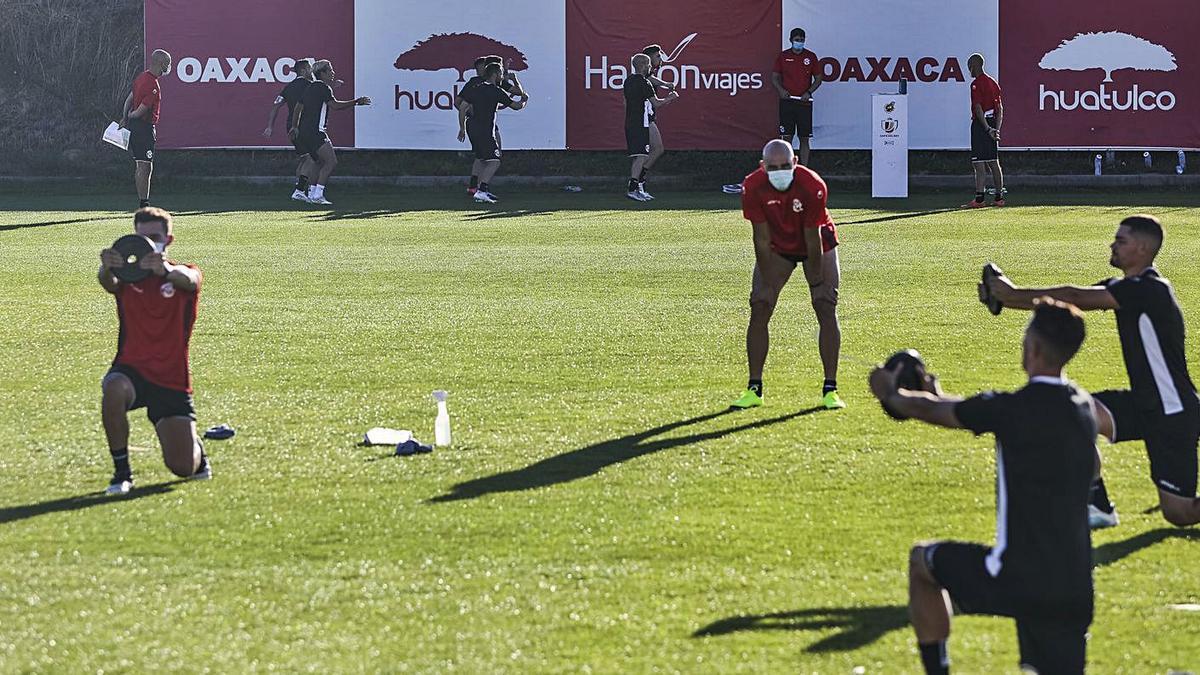 Varios jugadores hacen ejercicio al ritmo de una música al fondo de la imagen, mientras otros trabajan con un peso en primer término. | Nico Rodríguez