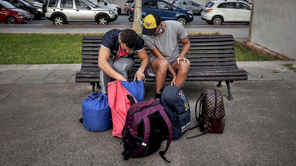 Dos migrantes en la plaza de s'Escorxador esperan las instrucciones de Cruz Roja, ayer.   B.RAMON