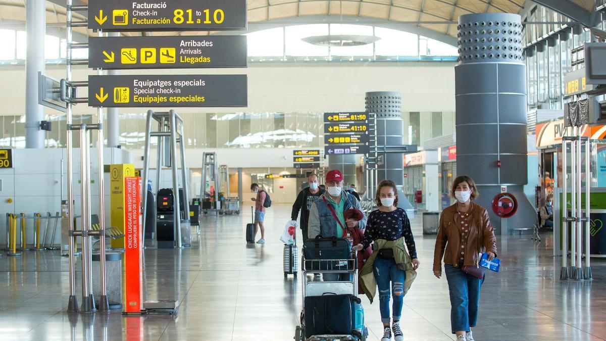Pasajeros protegidos con mascarillas en el aeropuerto