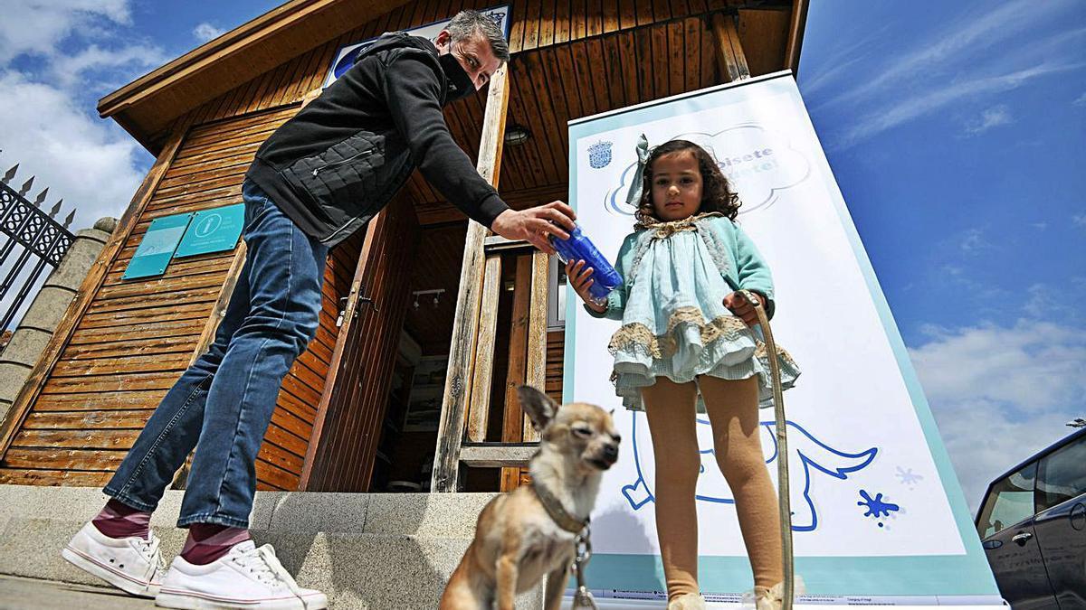 Uno de los propietarios de un perro recogiendo la botella para limpiar los orines.   | // GUSTAVO SANTOS