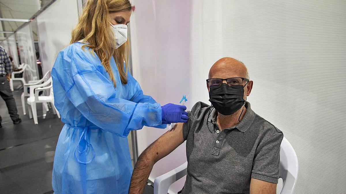 Un hombre se vacuna contra el coronavirus en el centro de vacunación de Les Arts. | PERALES IBORRA