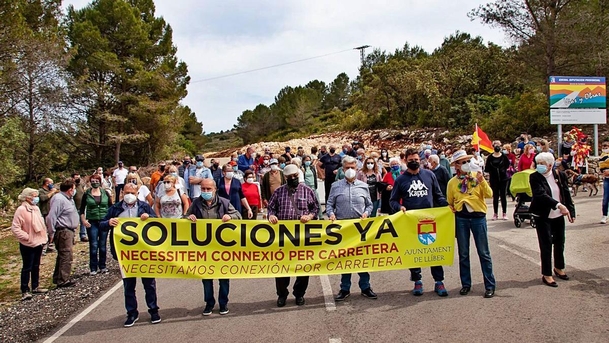 El alcalde de Llíber, José Juan Reus, con la pancarta que reclama la reapertura de la vía   VICENTE  BOLUFER