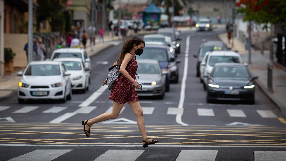 Una chica con mascarilla para protegerse del virus corre por Santa Cruz.