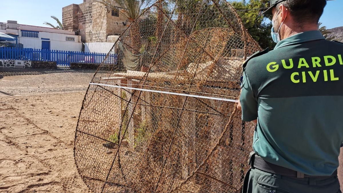 Un agente de la Guardia Civil junto a una de las nasas incautadas en Fuerteventura.
