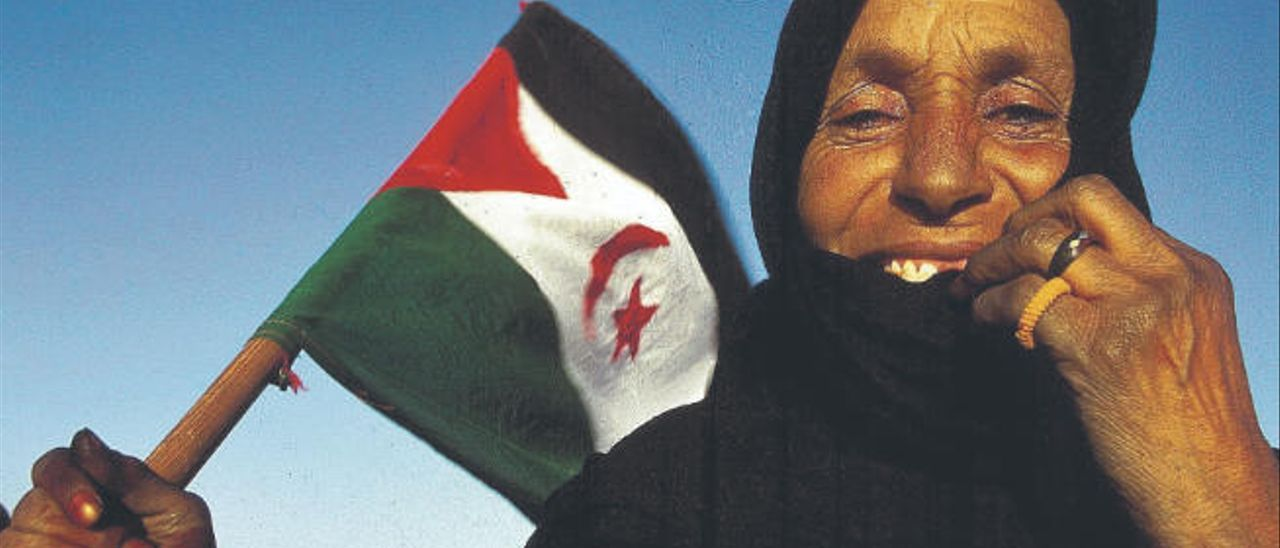 Una mujer porta una bandera saharaui en los campamentos de refugiados de Tinduf, en Argelia.