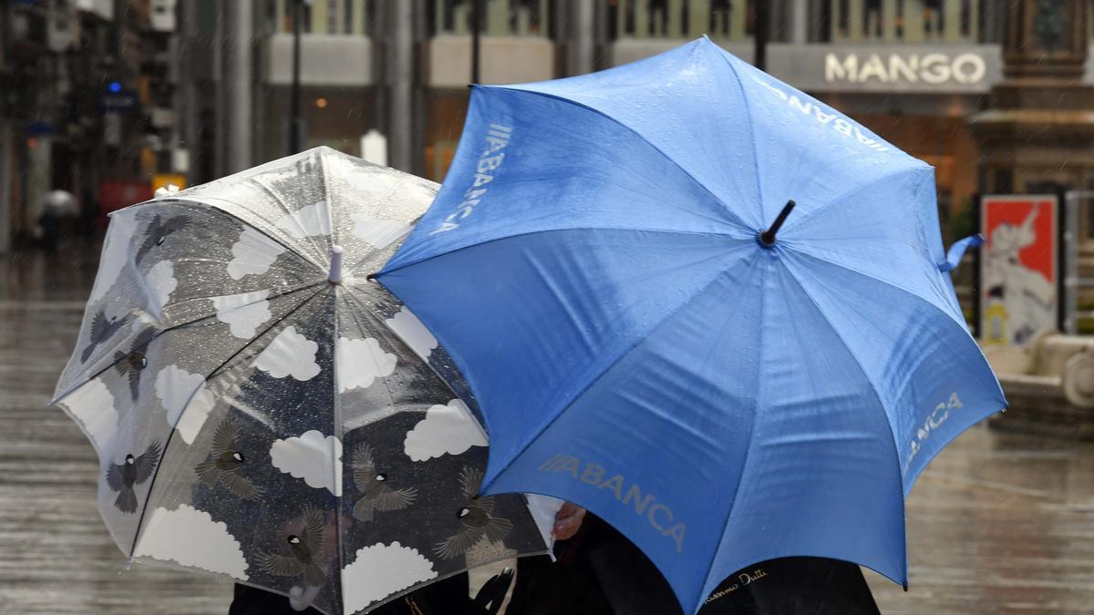 Dos personas se protegen de la lluvia.