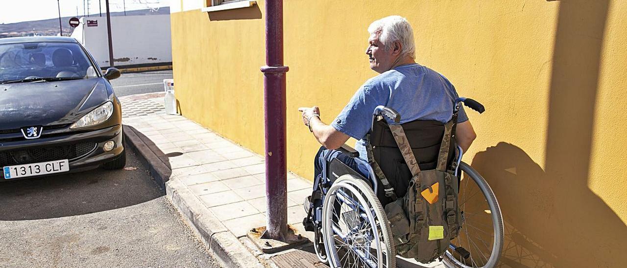 Eduardo Medina circula con su silla de ruedas por una calle de la capital debiendo sortear diversas barrera arquitéctonicas.