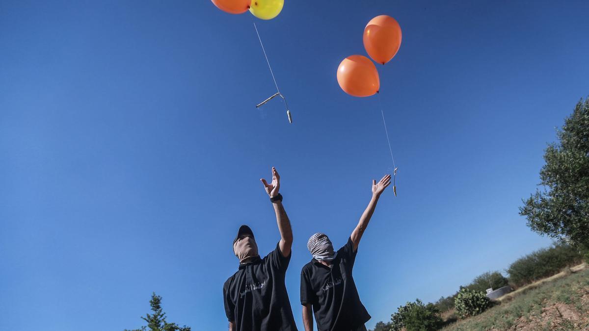 Un grupo de palestinos lanzan globos incendiarios desde Gaza con destino a Israel.