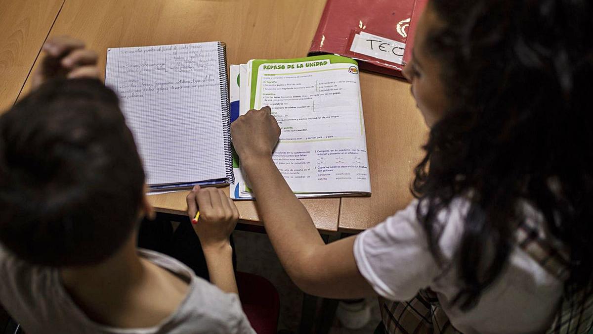 Dos niños hacen sus deberes en un aula de clases particulares. | Emilio Fraile