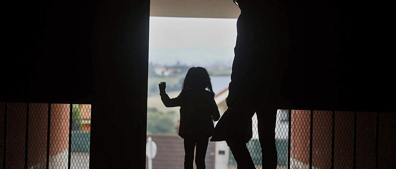 Una niña a punto de salir a la calle desde su domicilio.